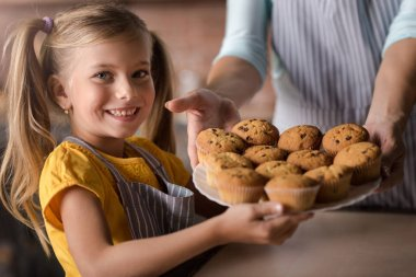 Delighted girl holding plate full of muffins