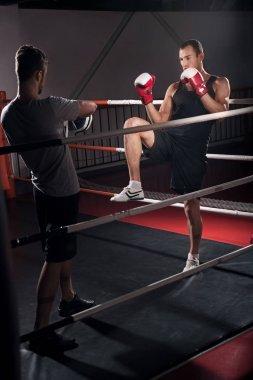 Men training kick boxing hook