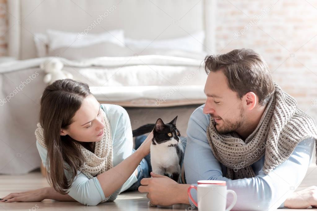 72c1c99f3dc9 Αφού τα κατοικίδια ζώα. Ευχάριστη ωραίο νεαρό ζευγάρι ξαπλωμένο στο πάτωμα  και κοιτάζοντας τη γάτα ενώ χαϊδεύει το — Εικόνα από yacobchuk1