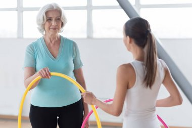 Joyful pleasant women holding a yellow hula hoop