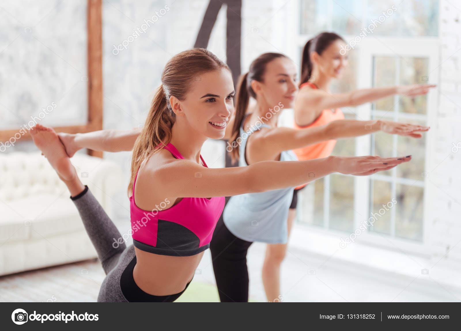 Three graceful women having group stretching classes — Stock