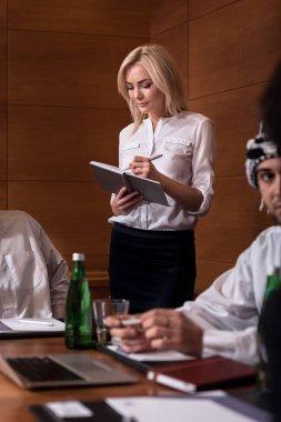 Young beautiful secretary making notes