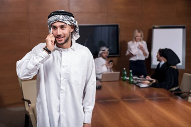 Happy looking Arabian man holding a phone