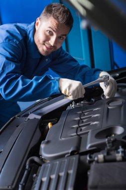 Cheerful handsome mechanic working in auto center