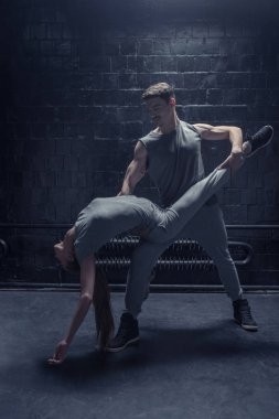 Delighted dancers performing in close interaction with each other
