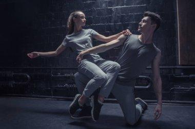 Involved dancer sitting on the leg of other athlete