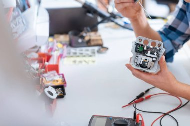 Close up of young man repairing drones chip with screwdriver