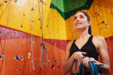Overjoyed woman using climbing equipment