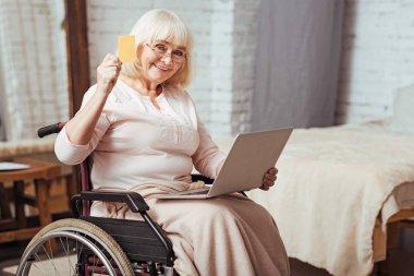 Positive elderly woman using laptop