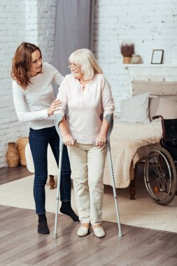 Positive woman helping he grandmother to walk with crutches