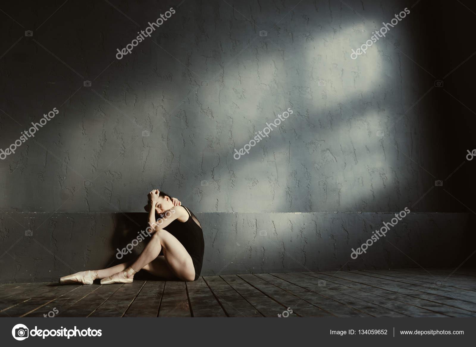 Boos jonge turnster zitten in het donker verlichte kamer