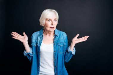 Confused elderly woman standing on black background