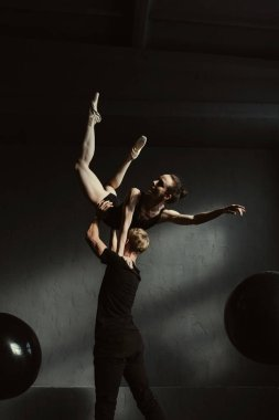 Skilled young gymnasts dancing together in the black colored studio
