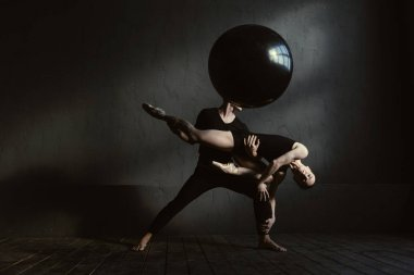 Muscular gymnasts performing in interaction with each other