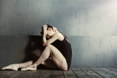Exhausted ballet dancer crying in the dark lighted room