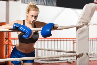 Fit determined boxer girl leaning on the ropes