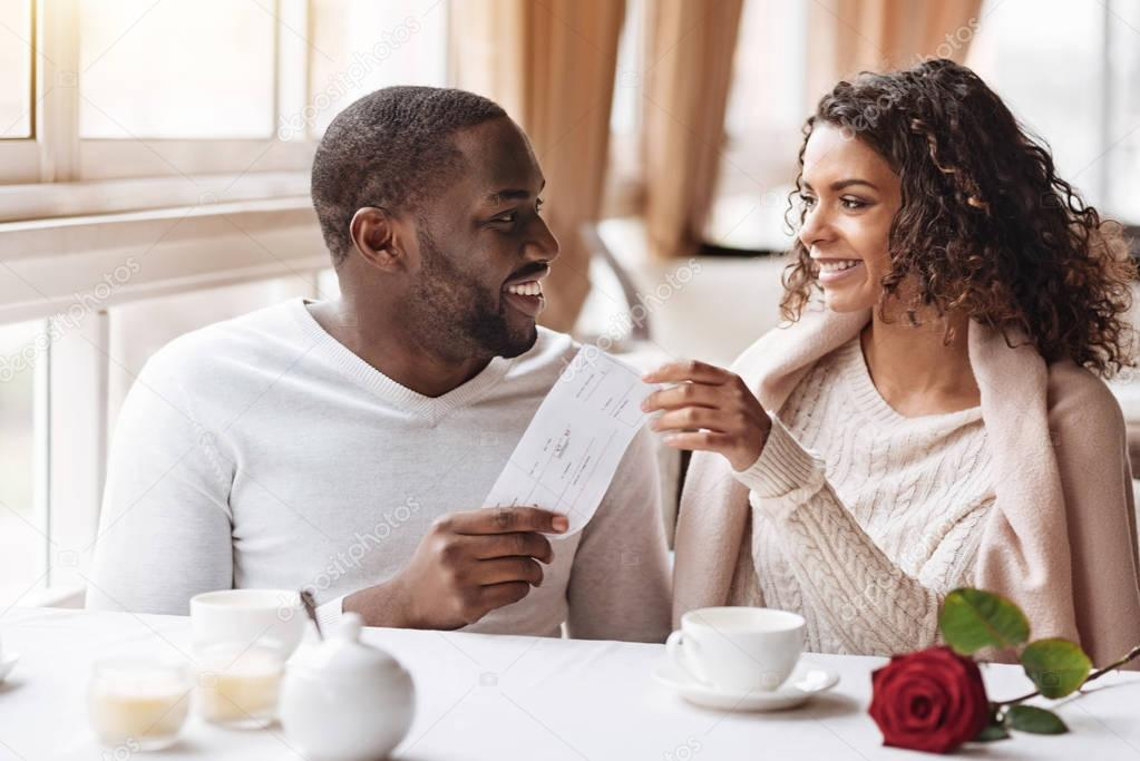 Delighted African American man giving a present to the woman