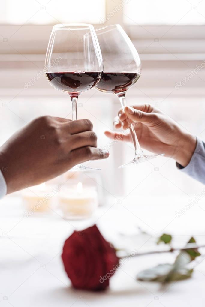 Hands of the African American couple holding wineglasses