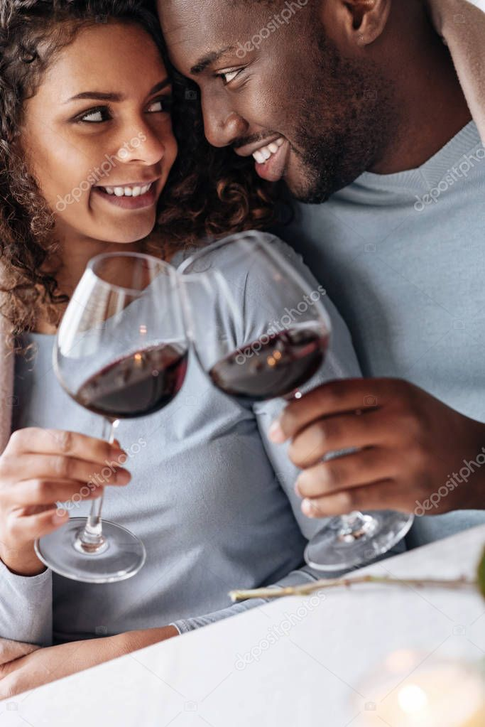 Passionate African American couple drinking wine in the restaurant