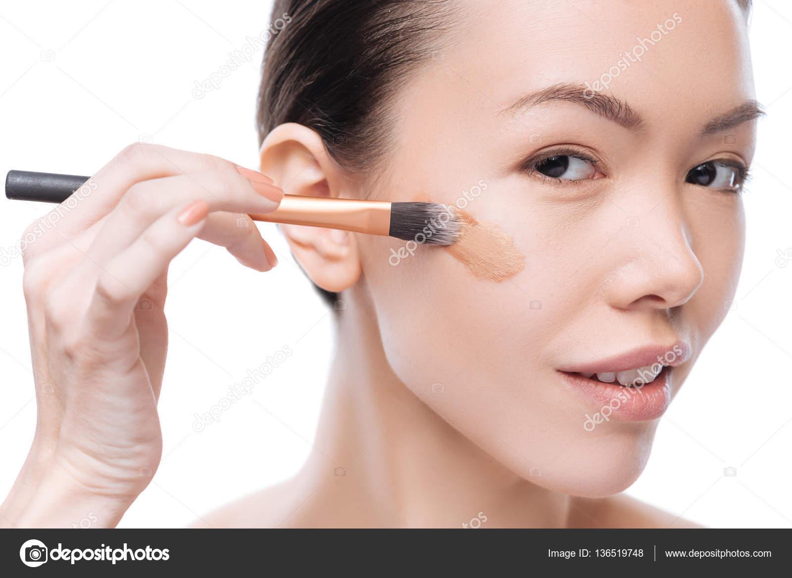 Feliz mujer positiva aplicando base maquillaje — Foto de Stock #136519748