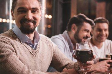 Pleasant joyful man raising his glass