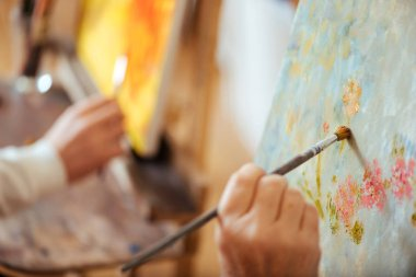Close up of two artists hands painting pictures with brushes