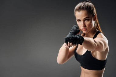 Powerful woman boxing on a grey background