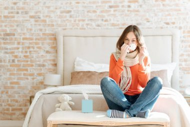 Upset young woman suffering from influenza at home