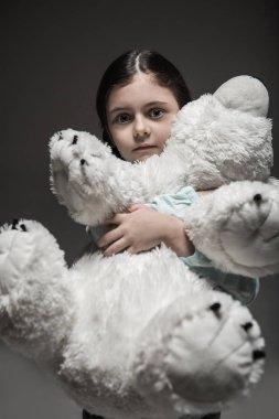 Frightened girl holding big white bear