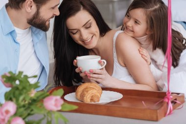 Positive good looking woman having coffee