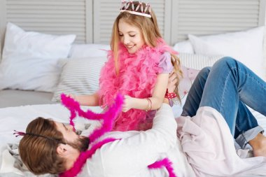 girl sitting near father and playing on bed