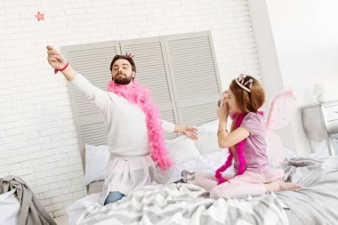 daughter taking picture of father on bed
