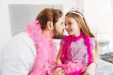 bearded man sitting close to daughter