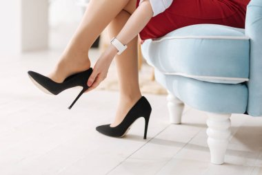 woman taking off high heel shoes