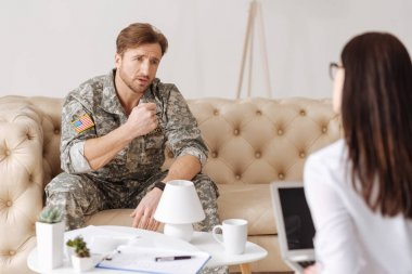 military man sitting on sofa at psychologist
