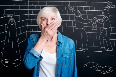 Shocked aged woman covering mouth