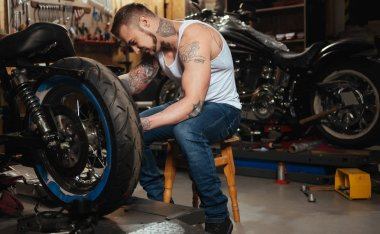 Positive delighted brutal biker fixing wheel
