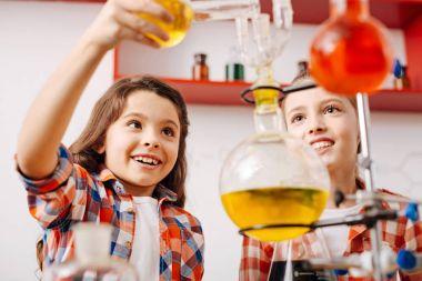 Girls holding chemical flasks