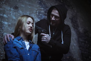 Man pointing gun at woman head