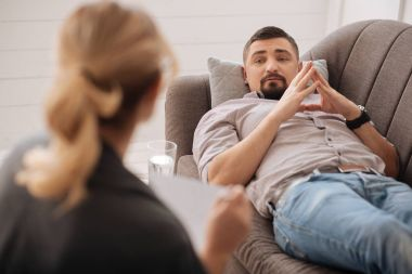 bearded man lying on couch