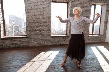 Aged woman dancing in ballroom