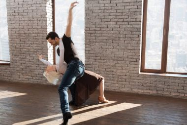 Proficient dance instructor tangoing with elderly woman at the ballroom
