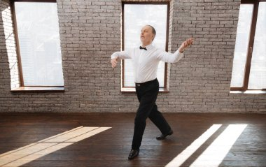 Diligent elderly man performing classical dance at the ballroom