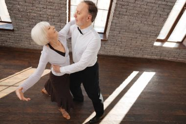 Cheerful aged couple waltzing at the ballroom