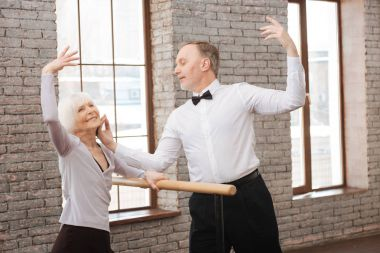 Active graceful pensioners dancing in the art studio