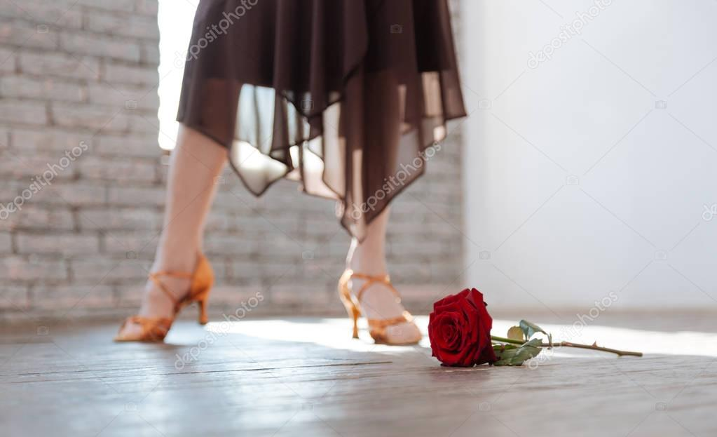 Passionate aged woman dancing tango at the ballroom