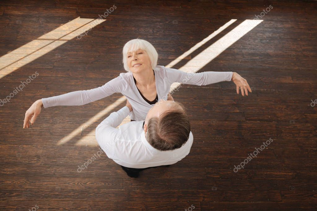 Delighted senior couple tangoing in the dance studio