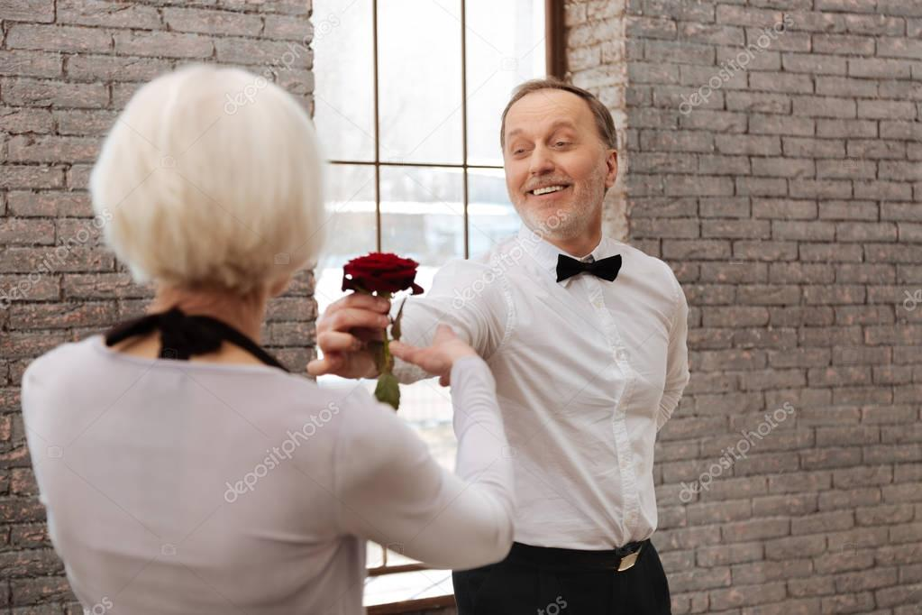 Smiling senior man dancing with aged woman in the ballroom