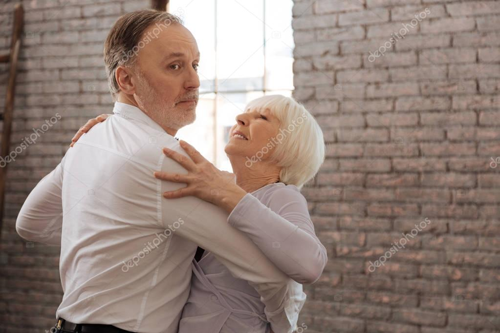 Involved aged dance couple waltzing in the dance studio
