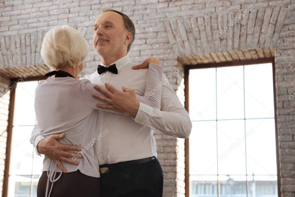 Optimistic aging dance couple enjoying waltz in the dance studio